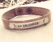 """genuine leather cuff w/ hand-stamped tag, """"be uncommon"""""""