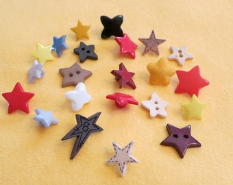 """22 Mixed plastic  craft star shaped buttons. Sizes 0.25"""" ins to just over 0.5"""". The longer pointed one is 1"""" in across.  LB12.11-13.12-1."""
