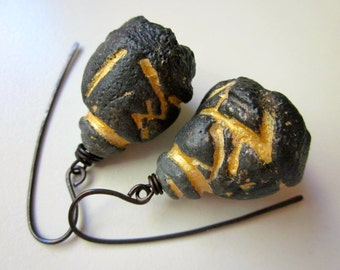 Sin Melts Into Light - primitive organic weathered coal black and gold shimmer polymer clay bell pod flower & oxidized copper earrings
