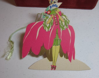 Gorgeous unused die cut gold gilded art deco 1920's Buzza place card colonial lady in powder wig wears elaborate pink gown holds deco fan
