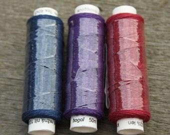 Three spools of linen thread - dark blue, dark red and purple