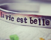 La vie est belle  french meaning of life is beautiful available in  aluminum /copper/brass bracelet 1/4 inch wide