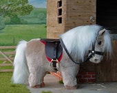 Shetland pony plush fur fabric model toy, palomino, with leather saddle and bridle. For children or collectors.