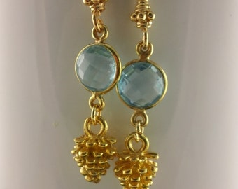 Pine Cone II: Faceted Sky Blue Topaz and Pine Cone in vermeiil dangle. Bezeled sky blue topaz