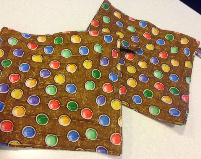 Set of two quilted hotpads with loops for handing. Brown with polka dots.