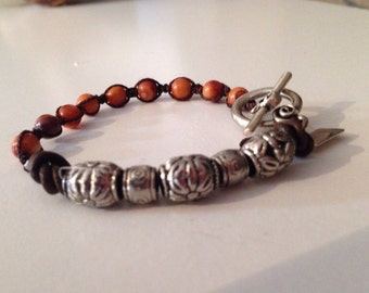 Beaded bracelet handknotted on chestnut silk. Leather and silver plate beads.