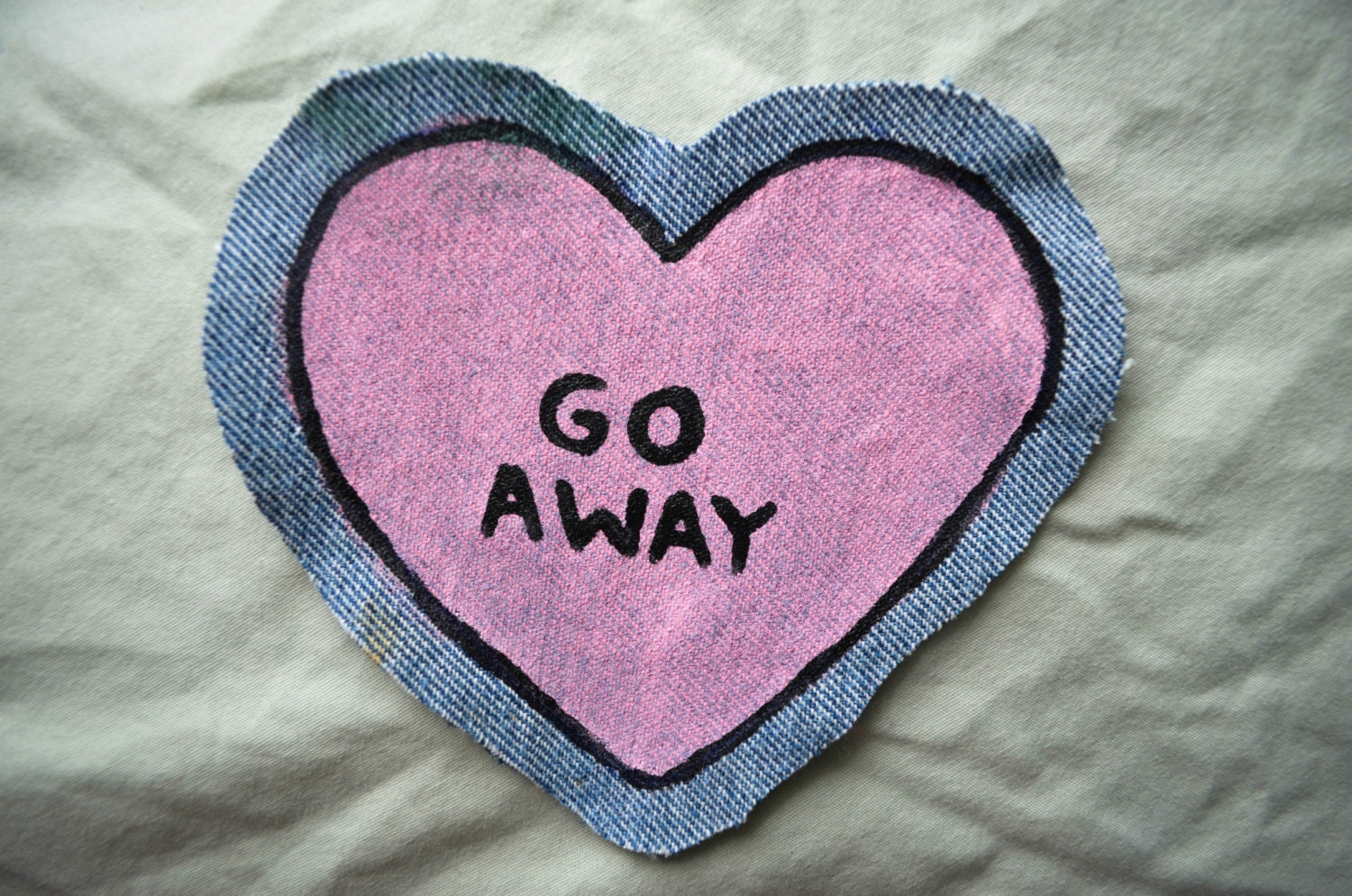 pink heart GO AWAY patch on denim