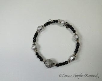 Delightful Black and Silver Bracelet with Cross Dangle