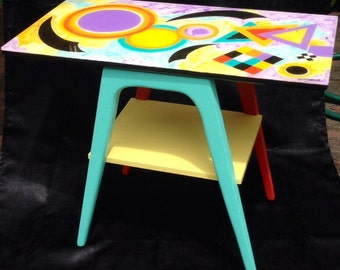 Modern art adorns the tops of these two beautifully designed and hand painted end tables.