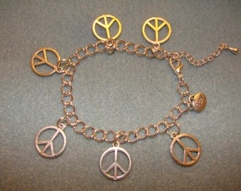 Charm Bracelet With Charms of The Peace Sign On A Silver Tone Link Chain
