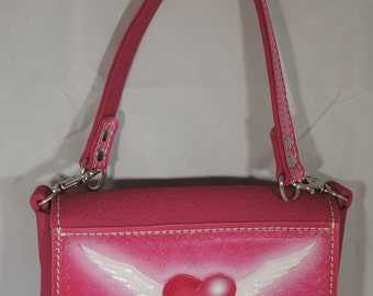 Purse - Ladies - Leather - Heart and wings in pink.  Changes to hip bag or belt loop purse w/o handle.  Measures 7 1/2 x 4 1/4 x 1 1/2.