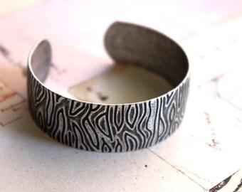 cuff bracelet. silver ox with a wood grain look
