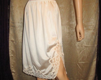 Vintage half slip, Size Small, Beige nylon, 3 and 1/2 inch lace edge trim and 9 inch side lace trimmed slit on 1 side, Made in USA,