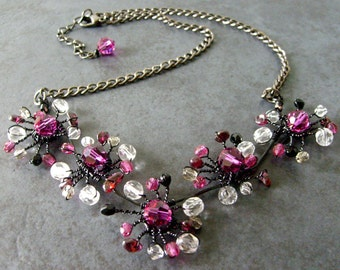 Flower Necklace. Twisted wire flowers in fuchsia pink, black, grey, clear crystal and garnet with gunmetal chain. Floral feminine choker.
