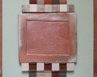 Handmade Wood-Fired Tile mounted on wood plaque and framed with mosaic tile