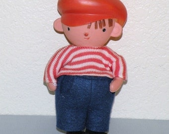 Older rubber doll with orange cap and clothing