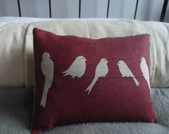 new hand printed  muted red bird on a wire cushion