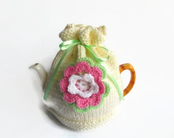 hand knitted tea  cosie with cozy crochet flower