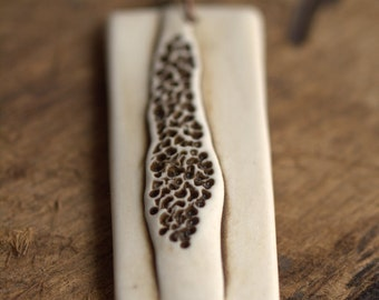 Delicate decay.  An earthy porcelain pendant with pitted texture.