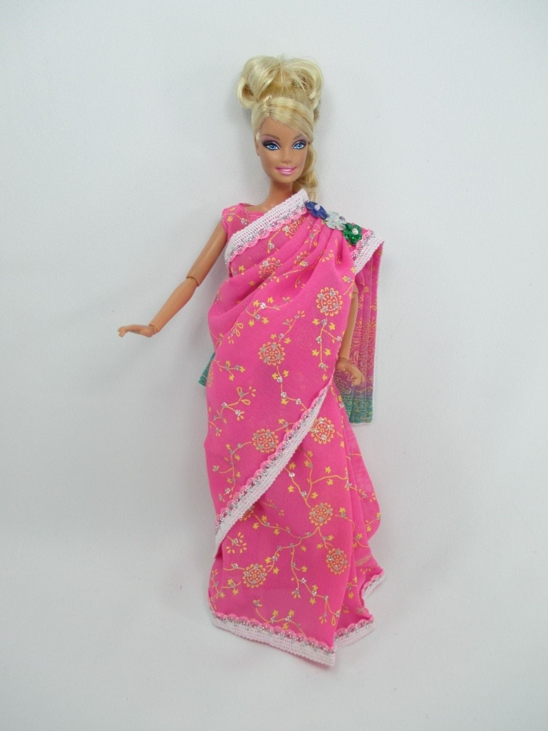 """traditional indian barbie India barbie wears a mustard-yellow sari with a matching hajib-like veil golden shoes, """"gold"""" bangles and touches of red complete her traditional look, while a monkey friend highlights the country's natural wildlife."""