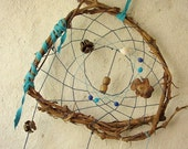 Baby mobile earth art magical dream catcher weaved in 2 shades of blue with a black pod, peacock  feather and many natural surprises.