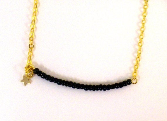 Gold chain with black beads and  tiny star.