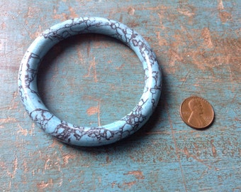 Solid turquoise colored stone bangle with veining.