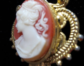 "Lovely vintage cameo pendant.  'Shell 'shows lady in profile set in gold toned metal. scroll work frame. 1.25"" long. BC14.4-12.5."