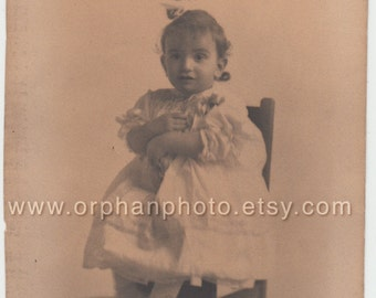 Vintage/Antique adorable photo of a cute little girl in a dress sitting on a chair