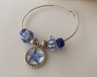 Wire bangle bracelet with blue glass beads and starfish charm.