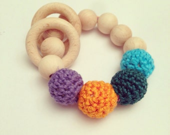 Baby green, orange, lilac, ultramarine blue teething ring toy with crochet wooden beads. Rattle for baby.