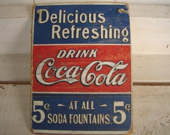 Shabby chic, vintage style coca cola advertising image sealed onto wood.Fun vintage ephemera.