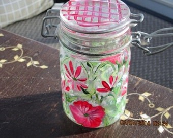 Storage container with red flowers, baby breath and green leaves