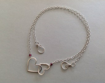 Hand formed sterling silver interlocking hearts and garnet chain necklace.