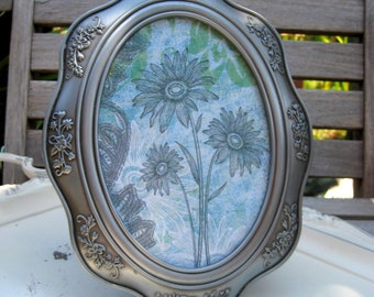 Vintage Silver Malden frame with a scalloped shape and Rose and vine detailing, sits on an easel back, blue floral image