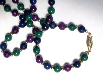 "Vintage necklace purple, green, blue stones with golden accent beads. About 24"" long."