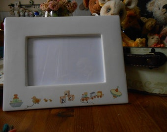 Photo frame for Baby picture cream ware china with toys as decoration Noah's Ark ABC spinning top toy train and Duck pull along.