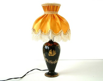 French vintage black porcelain boudoir lamp with gold enamel courtly love scene and a gold fringed lamp shade. Shabby chic.