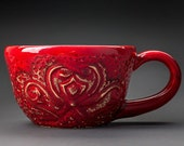 Red ceramic hand carved teacup with a heart and a bow