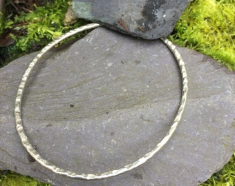 Silver oval bangle with textured hammered finish designed and handmade