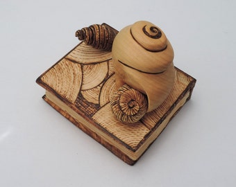 Handcarved and pyrographed Pinus Cembra wood sculpture - A collection of three snail shells upon a miniaturized book