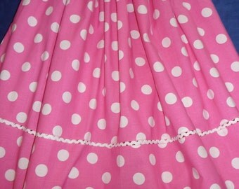 White polka dots pink dress with ruffle at the neckline.
