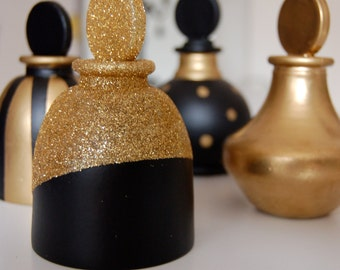 Set of four glass bottles painted in gold and black.