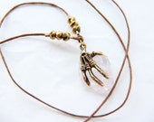 Skeleton hand grasping a rough cut Rose Quartz crystal necklace with gold crystal beads