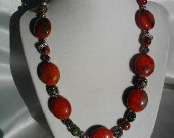 Statement necklace containing red beads with green accents along with metal beads.