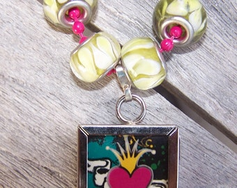 Reversible pendant with heart and crown image on one side and winged crown on the other.