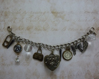 """Price Reduction! 8"""" Charm Bracelet: Brass heart with rhinestones, No. 20 charm, clear beads, clock, angel wing, bow, travel bag, and stakes"""