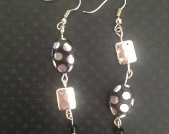 "The upside down earrings! These black glass beads are paired with silver ""dented"" metal to create a one of a kind look."