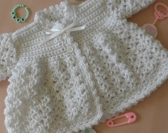White crocheted three to six month old baby boy or girl long sleeve