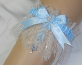 Blue garter with whisper soft, white lace dotted with crystal rhinestones and embroidered floral details
